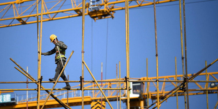 Image: A worker walks along scaffolding at a construction site in Beijing