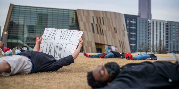 "Demonstrators participate in a ""die-in\"" peaceful protest outside of the World of Coca-Cola in downtown Atlanta on March 15, 2021."
