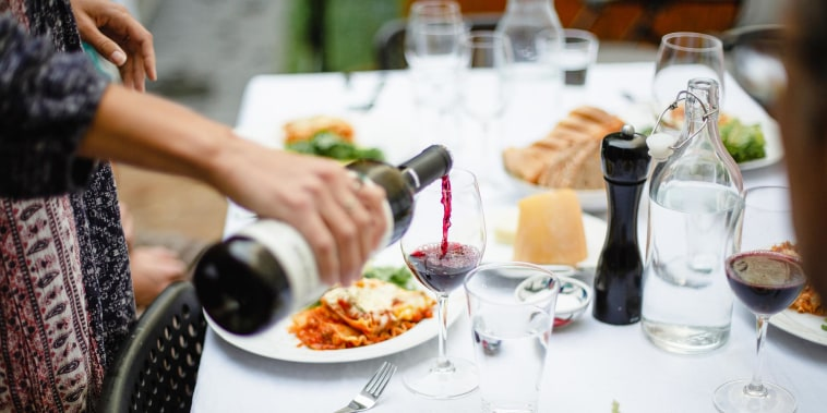 Woman pouring red wine at dinner