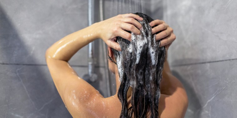 Woman washing hair in the shower with shampoo