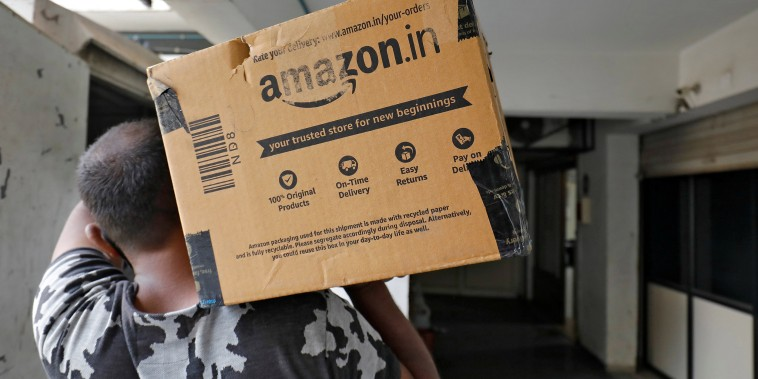 Image: An Amazon delivery worker carries a package to a customer at a residential apartment in Ahmedabad, India