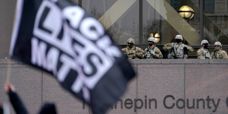 Image: National Guard members are seen as a person flies a Black Lives Matter flag during a rally outside of the Hennepin County Government Center