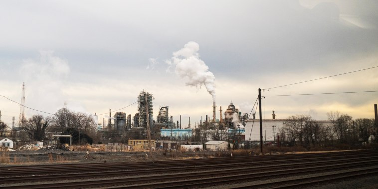 Industrial pollution pours from an oil refinery on Jan. 8, 2021, near New Castle, Del.