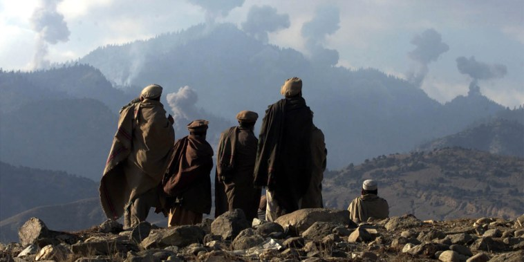 Image: AFGHAN FIGHTERS WATCH SEVERAL EXPLOSIONS FROM US BOMBINGS IN THE TORABORA MOUNTAINS.