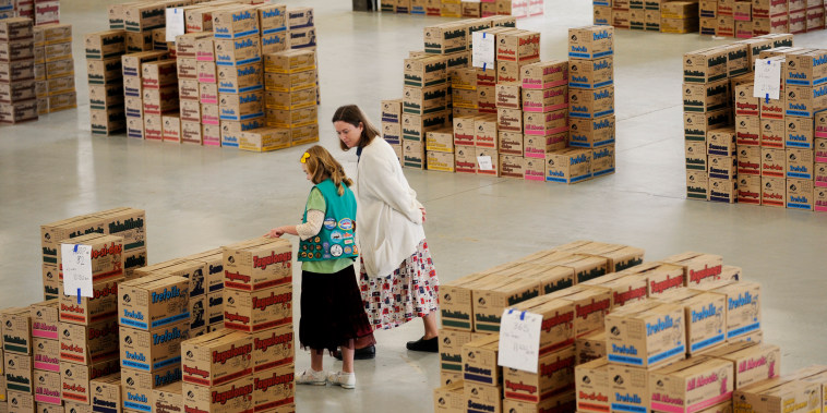February 12, 2008--12-year-old Liza <cq> Hein <cq> and her mother, Mary, of Longmont, look over boxes of Girl Scout cookies organized by troop and ready to be loaded into vans and trucks at the Girl Scout cookie distribution area located in an exhibition