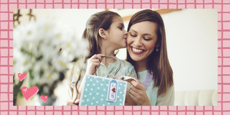 Daughter kissing her mother as she gives her a gift for Mother's Day