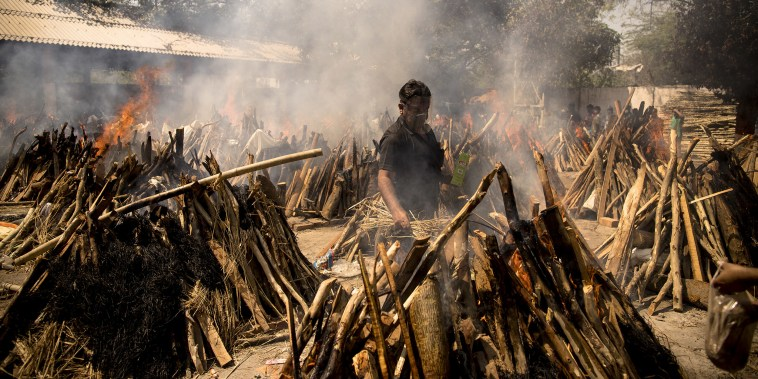 Image: A man performs the last rites of his relative who died of the Covid-19 coronavirus disease as other funeral pyres are seen burning during a mass cremation held  at a crematorium