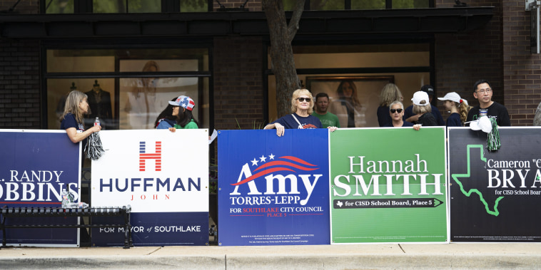 People hold campaign posters for various candidates in municipal elections in Southlake, Texas, on May 1, 2021.