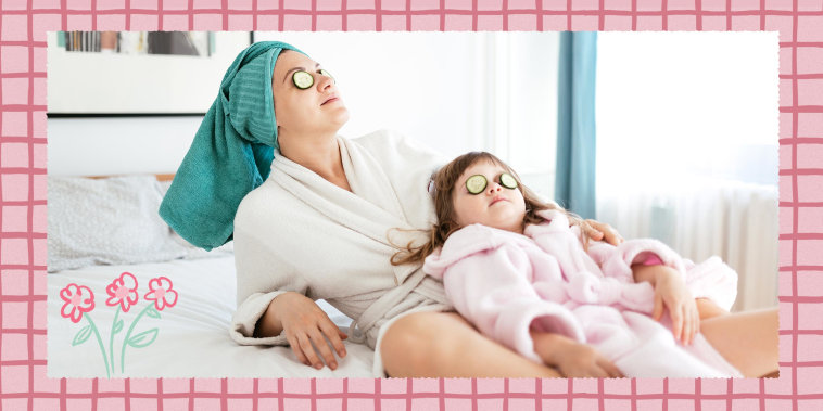 Mother and young daughter cleaning back on bed, wearing robes, towels on their heads and using cucumbers over their eyes