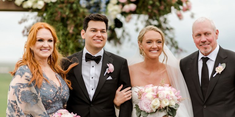 A mother and father stand proudly next to a smiling bride and groom