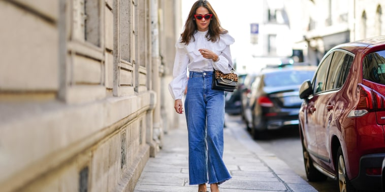 Woman walking down the street wearing flare jeans and a white shirt