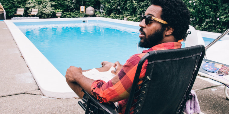 Man relaxing on a black chair by the pool