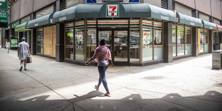 Image: Pedestrians pass in front of a 7-Eleven store in Chicago on Aug. 3, 2020.