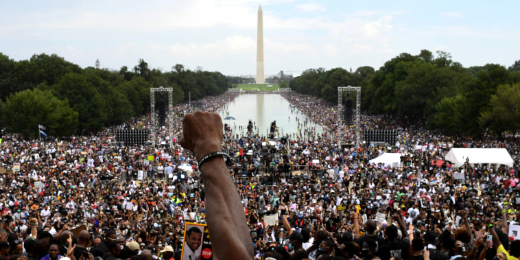 "Image:  participant raises his first during the ""Commitment March: Get Your Knee Off Our Necks\"" protest against racism and police brutality on Au. 28, 2020, at the Lincoln Memorial in Washington, DC."