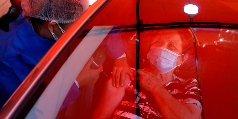 Image: An elderly woman gets a shot of the Astra Zeneca vaccine for Covid-19 from a car under a red tarp set up outside Trinidad Maternity Hospital in Asuncion, Paraguay