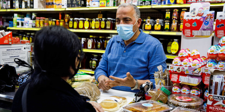 Hamed Nabawy Hamed explains to a customer how to prepare a dish at his halal grocery store Fertile Crescent in Brooklyn, N.Y., on May 5, 2021.