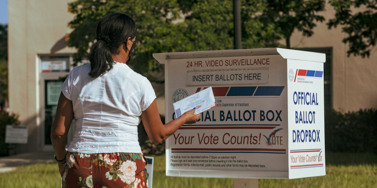 IMage: A woman puts a ballot in a drop box in West Palm Beach, Fla., on Nov. 1, 2020.