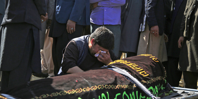 A man cries over the body of a victim of deadly bombings near a school on Saturday, at a cemetery west of Kabul, Afghanistan, on May 9, 2021.
