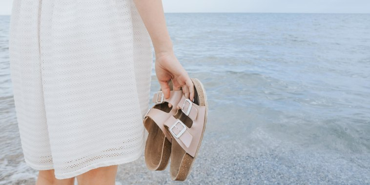 Woman in a white dress holds beach slippers in her hands and walks along the shore