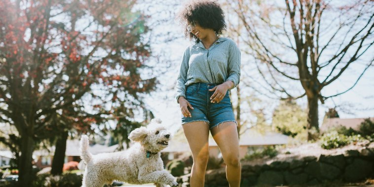 Woman playing at the park with her dog, wearing Denim shorts