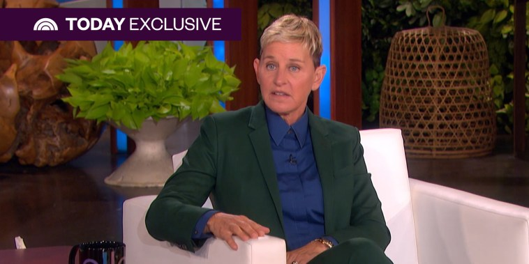 Ellen DeGeneres sits on a white chair on her TV show set in a green suit and blue collared shirt