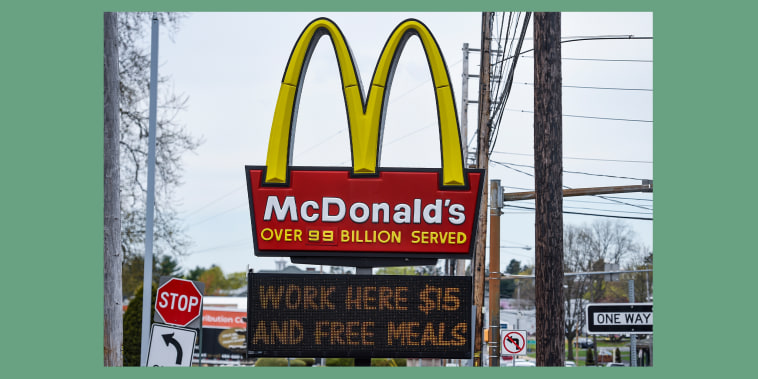 """The sign at the McDonald's restaurant on Penn Ave in Sinking Spring, PA April 19, 2021 with a message on a board below it that reads \""""Work Here $15 And Free Meals\""""."""
