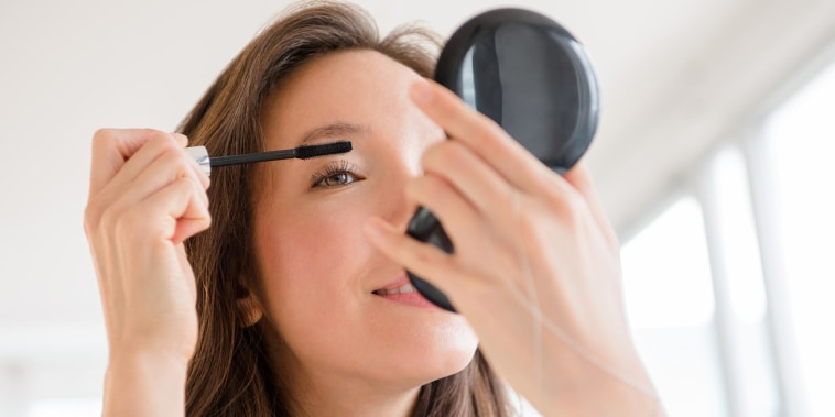Woman applying makeup mascara while looking in a compact mirror