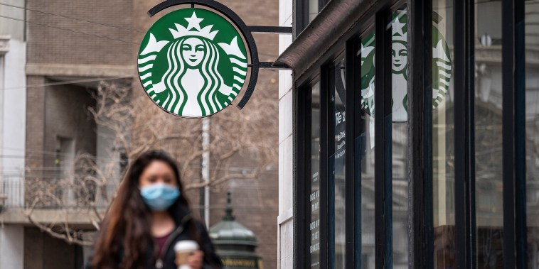 A person wearing a protective mask walks past a Starbucks coffee shop in San Francisco, California, U.S., on Thursday, Jan. 21, 2021.