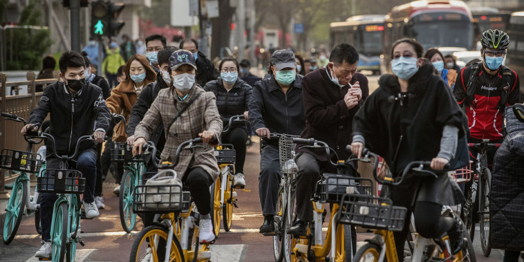 Image: Chinese commuters wear protective masks as they ride bikes and scooters in the central business district during rush hour