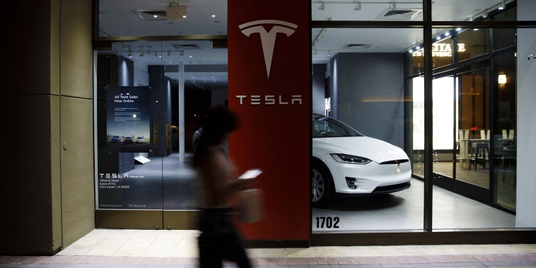Image: A pedestrian walks past a Tesla store in Palm Desert, Calif, on March 7, 2019.
