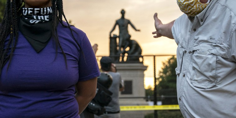 Image: Anais, 26, who wants to remove the Emancipation statue in Lincoln Park in Washington argues with a man who wants to keep it on June 25, 2020.