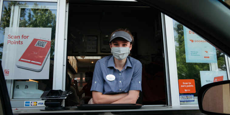 Image: An employee wears a protective mask while working the drive thru window of a Chick-fil-A Inc. restaurant in Bentonville, Ark.
