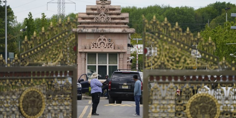 People stand near the entrance to the BAPS Shri Swaminarayan Mandir in Robbinsville Township, N.J., on May 11, 2021.