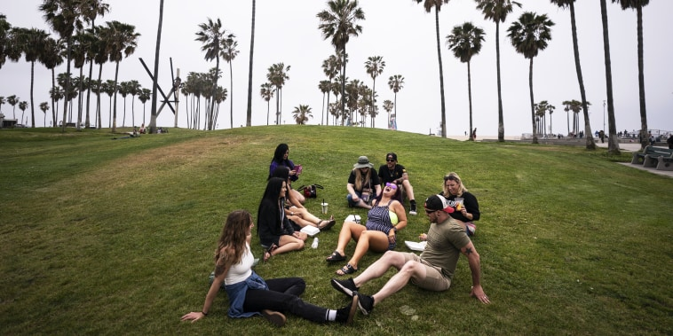 A group of friends, who said they are fully vaccinated for Covid-19, relax on the beach in the Venice section of Los Angeles on May 5, 2021.