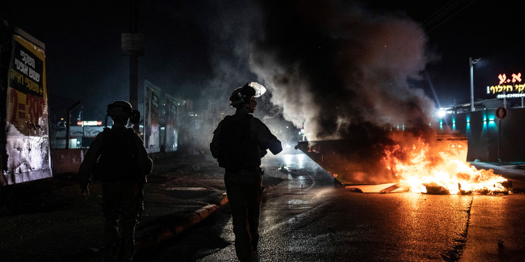 Image: Israeli police patrol during clashes between Arabs, police and Jews, in the mixed town of Lod
