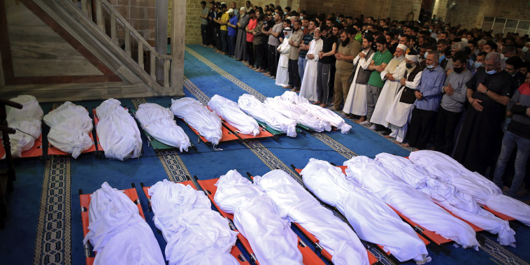 Mourners pray over the bodies of 17 Palestinians who were killed in overnight Israeli airstrikes in Gaza City on May 16, 2021.