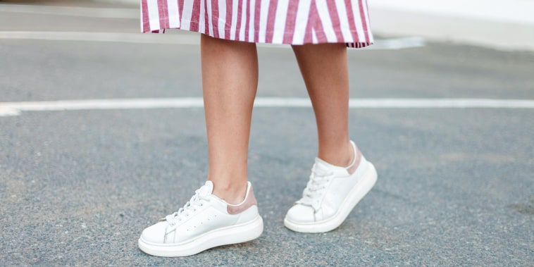 Woman wearing a pink and white striped dress with white sneakers