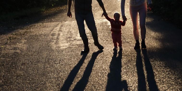 Family walking holding hands, long shadows