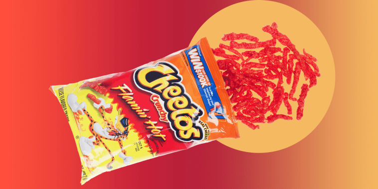 Opened bag of Cheetos Crunchy Flamin? Hot snacks with some pouring out onto white background