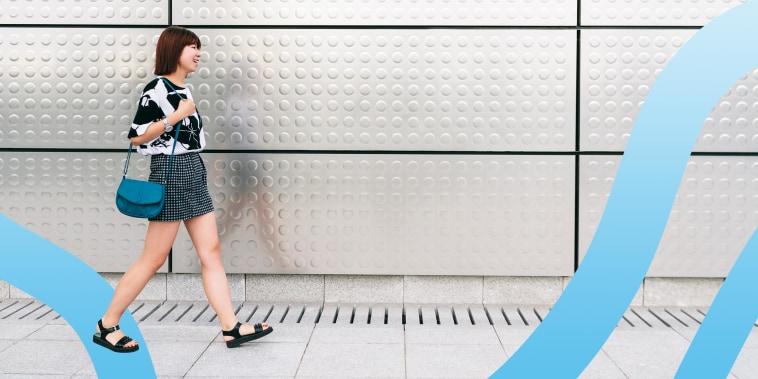 Woman walking on sidewalk, wearing black walking sandals