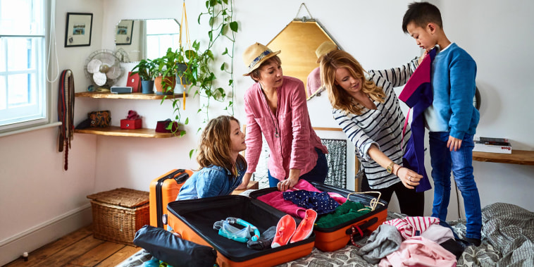 Couple packing suitcases for vacation with two children