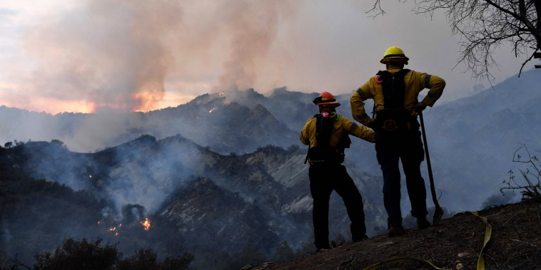 Firefighters work on a fire line as flames from the Palisades Fire glow in the distance in Topanga State Park, northwest of Los Angeles, on May 15, 2021.