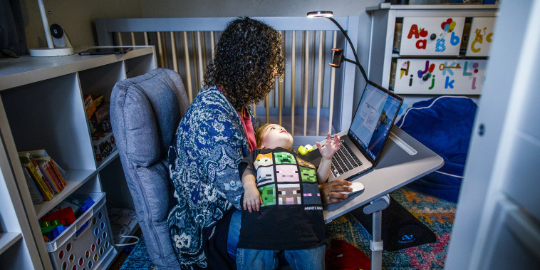 Image:; A mother works at her make shift office set up in her daughter nursery.