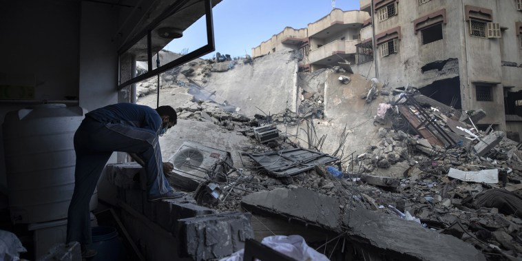 Image: A Palestinian man inspects the damage of a six-story building which was destroyed by an early morning Israeli airstrike, in Gaza City