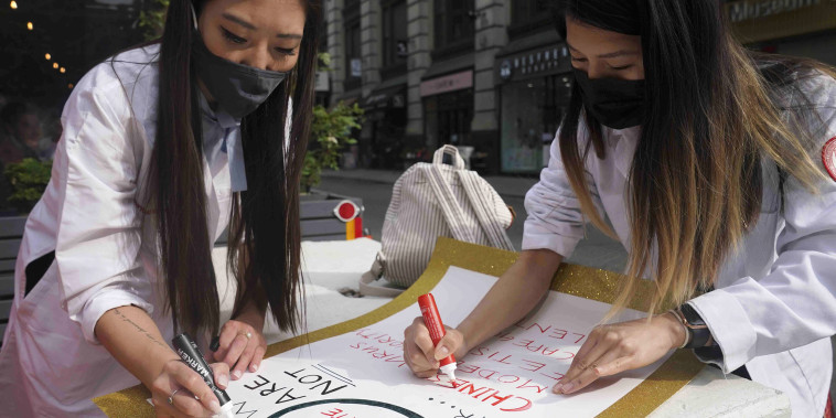 Image: Dr. Michelle Lee, left, a radiology resident, and Ida Chen, right, a physician assistant student, prepare posters they carry at rallies protesting anti-Asian hate