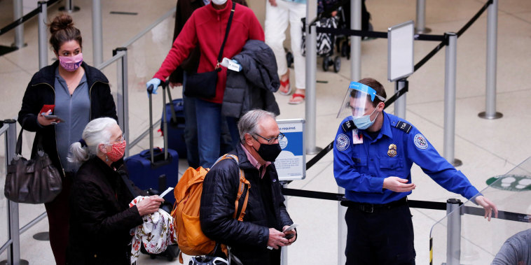 A TSA worker directs travelers to the next station at a security checkpoint at Seattle-Tacoma International Airport in SeaTac, Wash., on April 12, 2021.