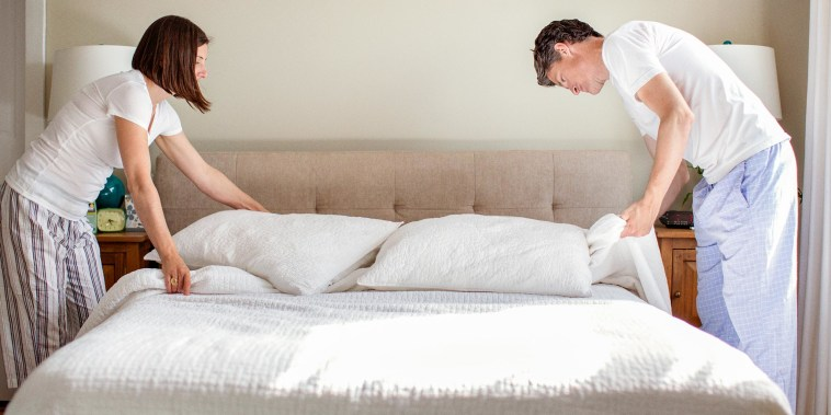 Couple arranging bed at home in their pajamas