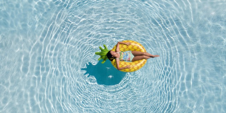 An aerial view of teenage girl relaxing in the swimming pool on a pineapple floatie