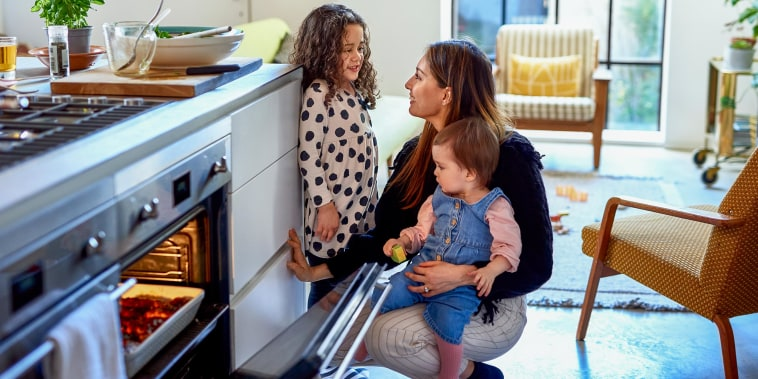 Mother cooking at home with two children