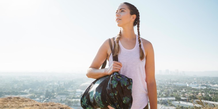 Woman carrying sports bag on hilltop in Los Angeles